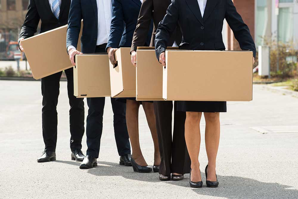 Business people holding boxes - protectionism