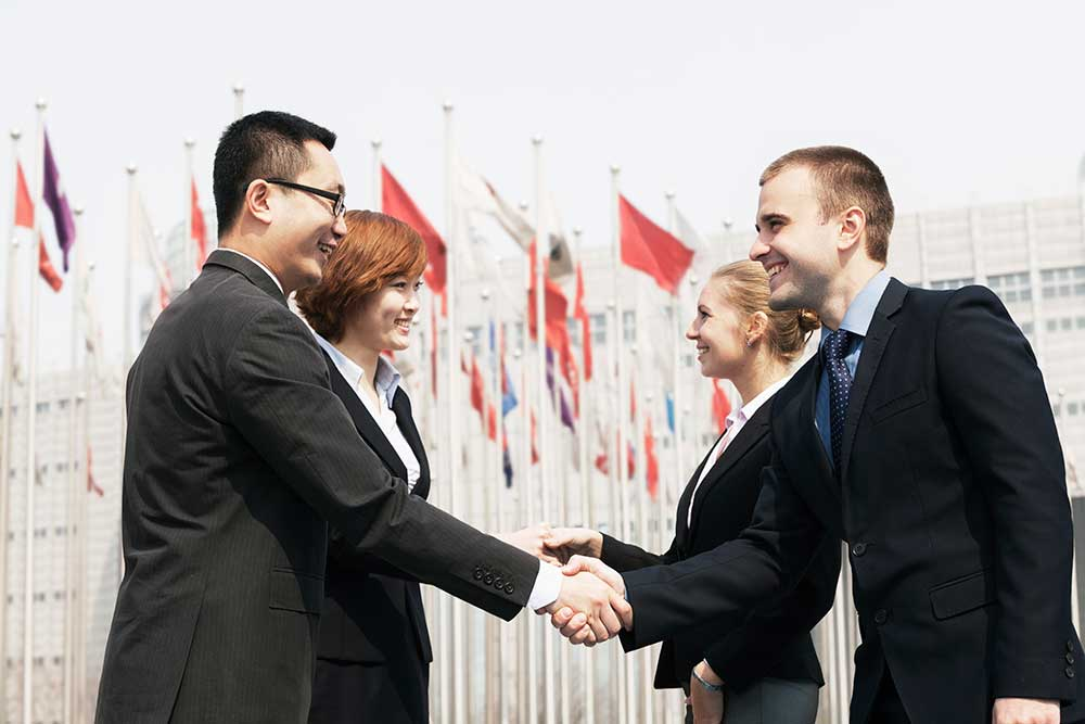 Shaking hands in front of WTO - Trade Facilitation Agreement
