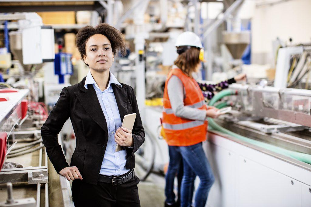 Female supervisor holds tablet in factory