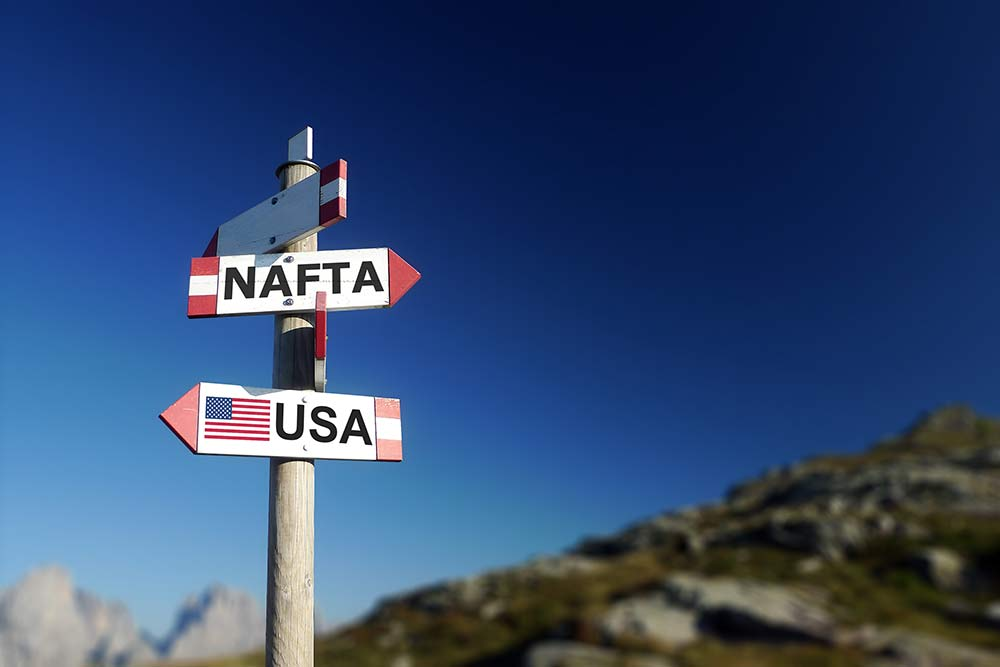 """Signpost with directional signs featuring """"NAFTA"""" """"USA"""" """"Canada"""" and """"Mexico"""""""
