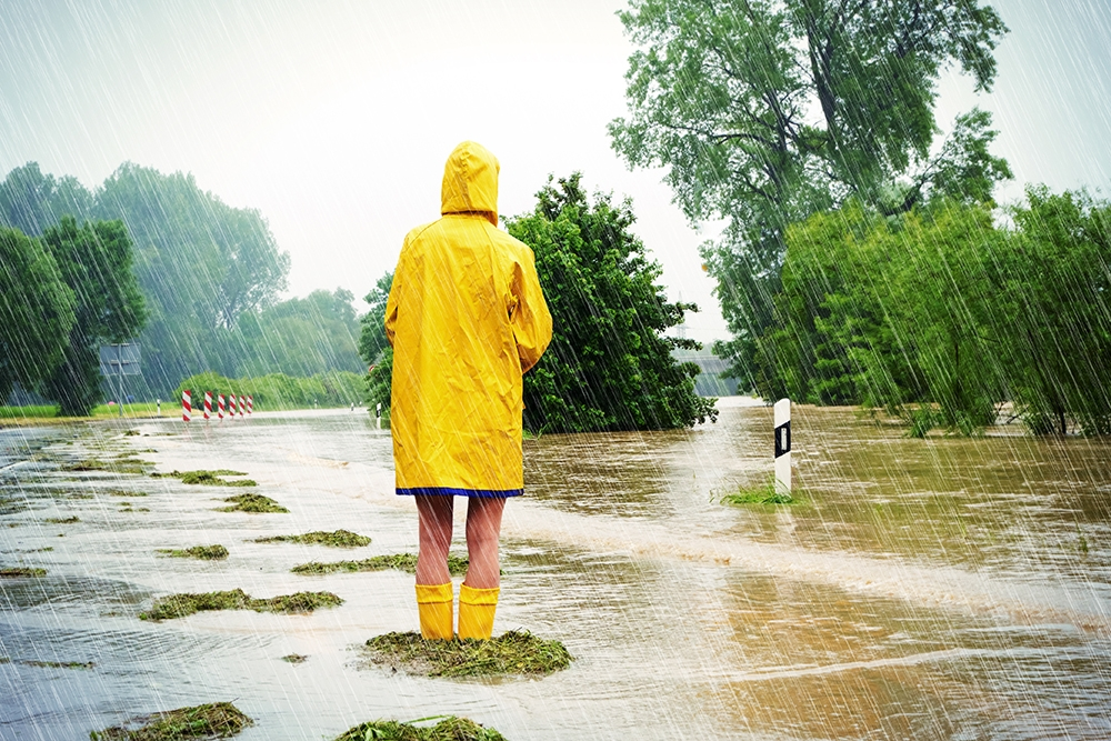 person in a raincoat standing in a flooded field