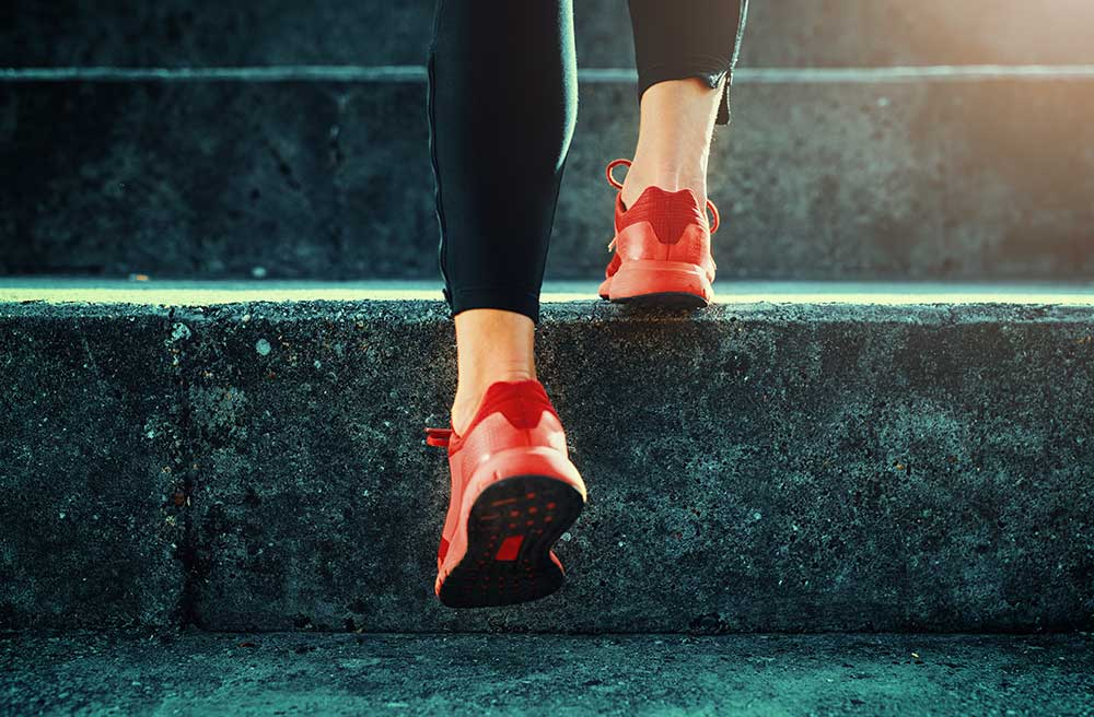 Runner in red shoes going up steps