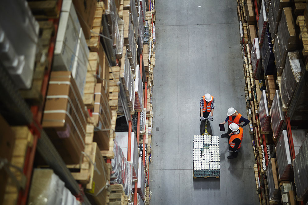 overhead view of 3 workers in a warehouse