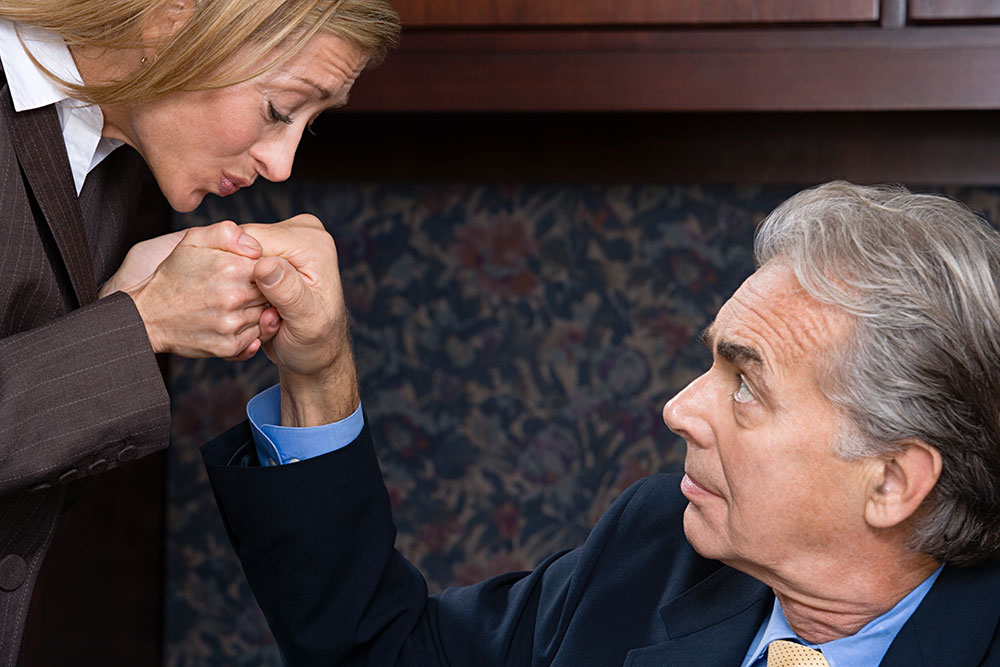 Business woman awkwardly kissing business man's hand