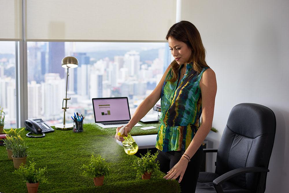 women watering plants at her desk