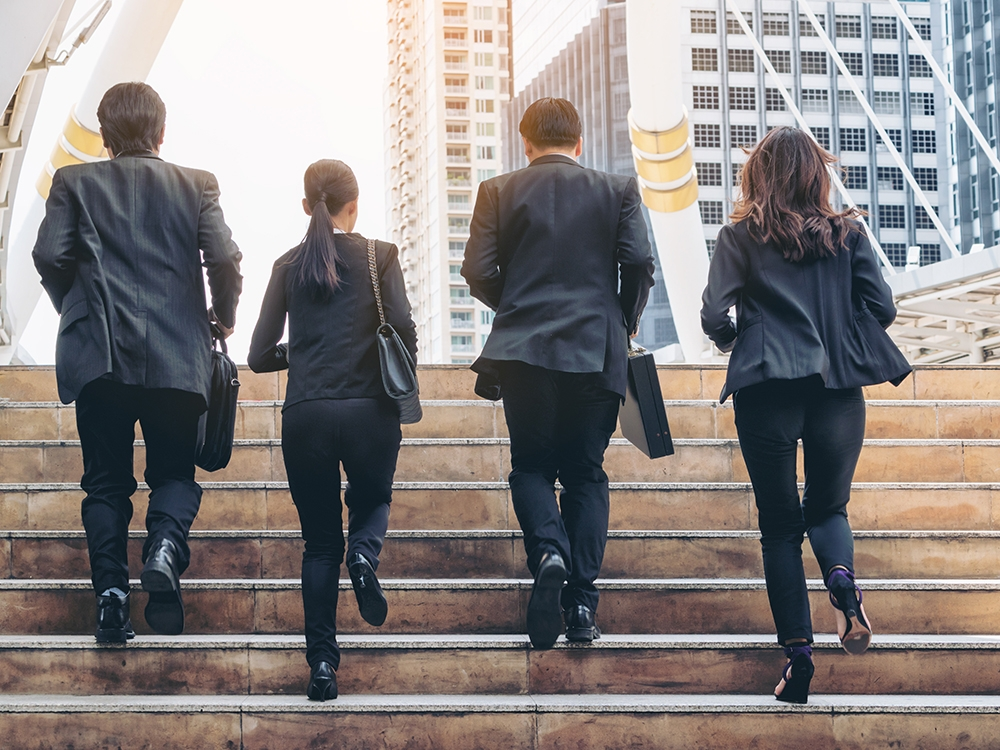Lively business team running in the city. Group of businessmen and businesswomen wearing full business suit with business buildings background.