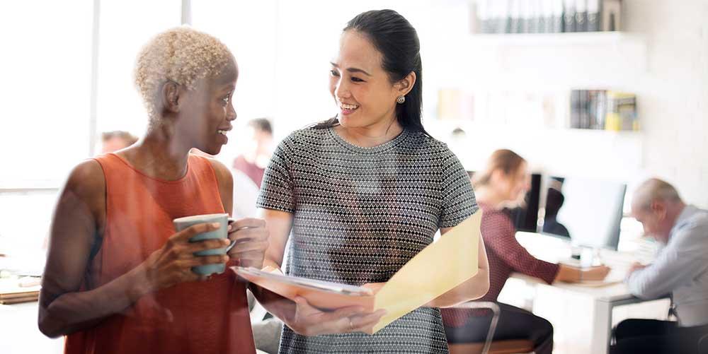 Business women discussing a folder of work