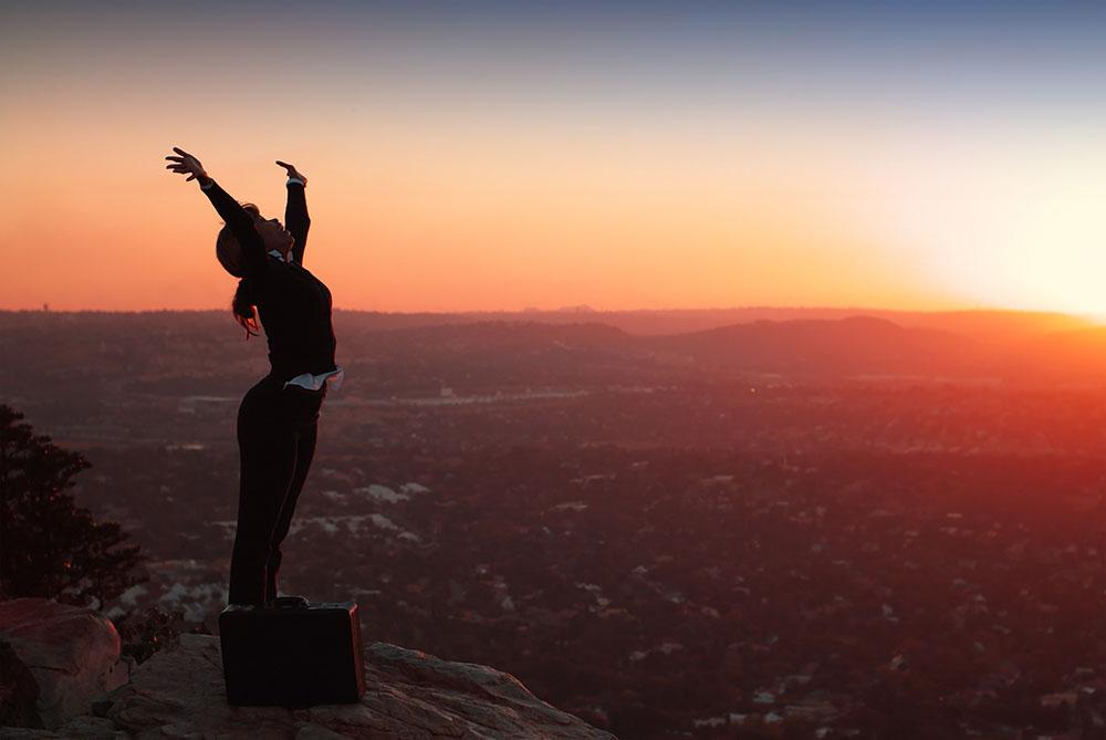 Happy businesswoman celebrating overlooking landscape sunset