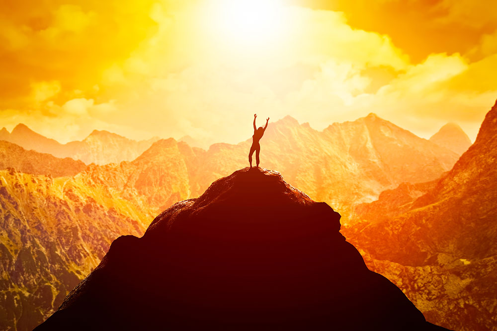 person standing on a mountain in golden sunlight