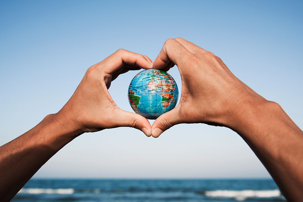 hands holding a miniature global in the shape of a heart