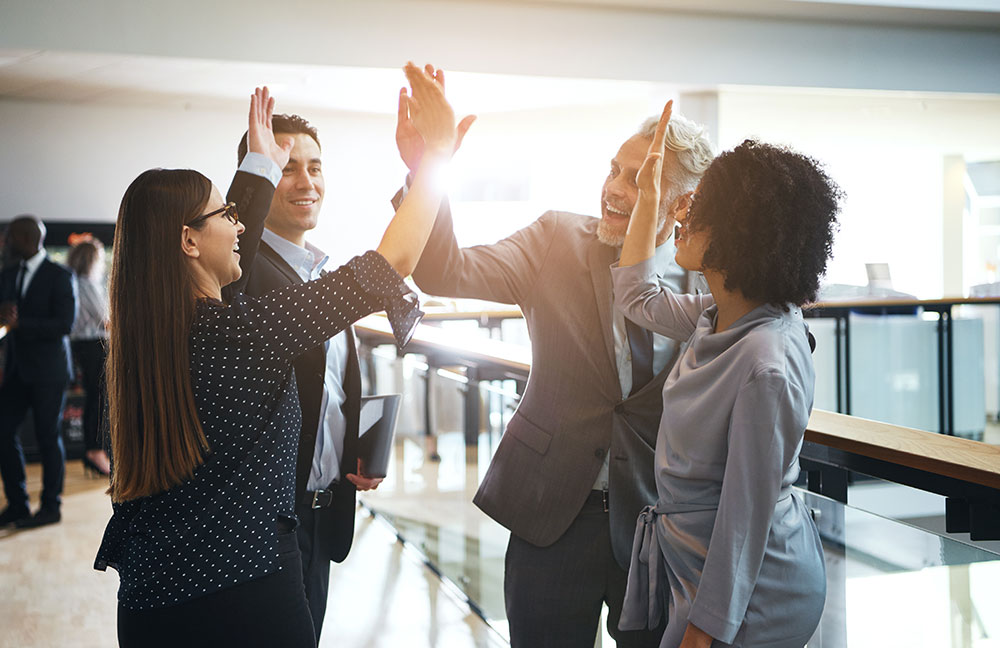 4 happy business people giving each other high fives