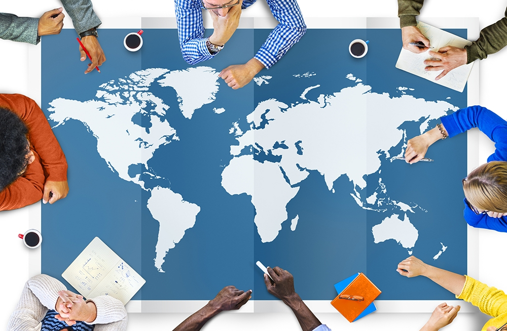 group of professionals working around a world map