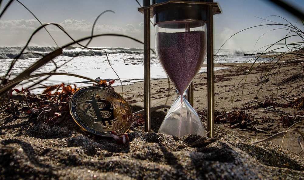 Bitcoin and hourglass on a beach