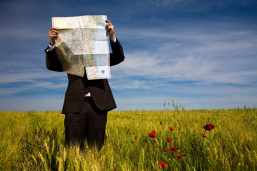 business man in field looking at map