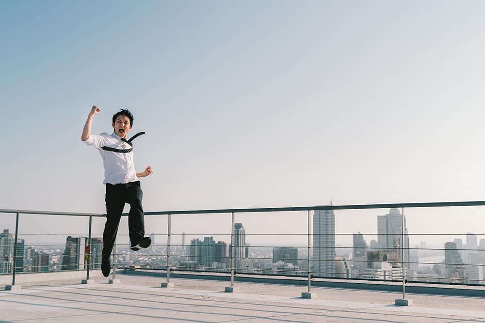 Business man celebrates by jumping in the air on rooftop