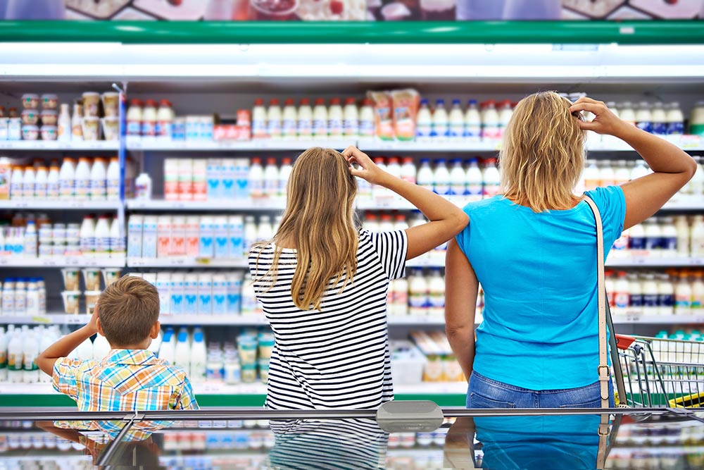 family confused looking at products in grocery store