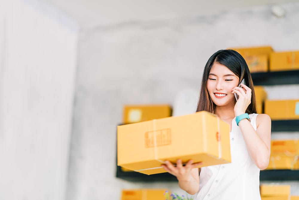 Young business owner on the phone holding a package