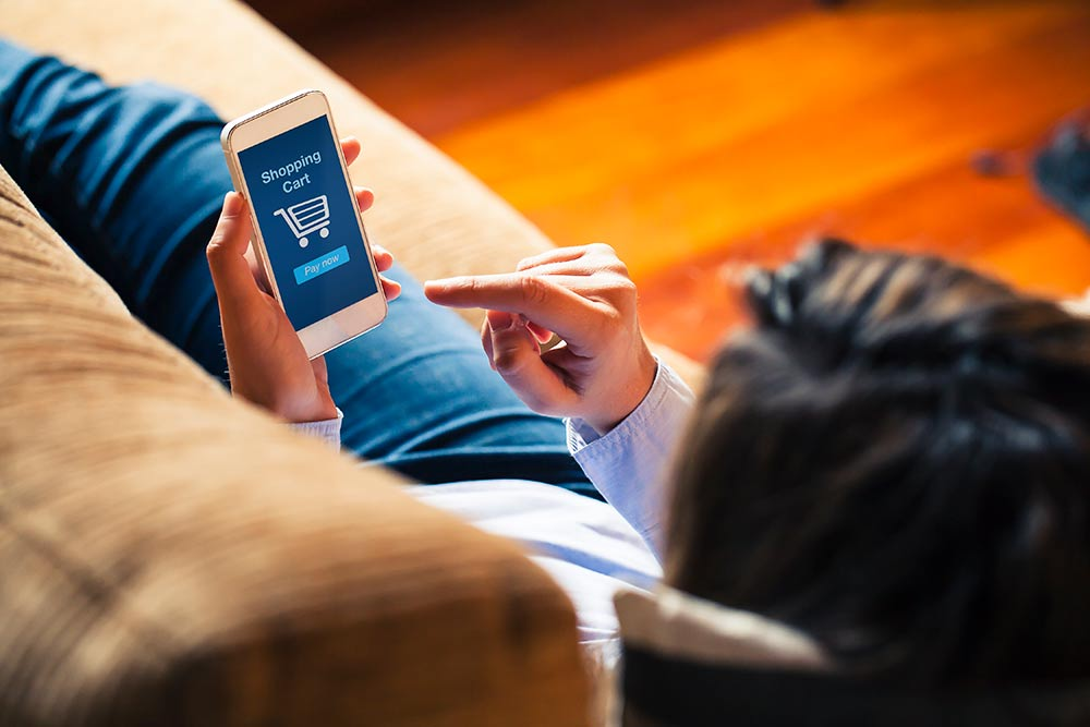 woman on couch completing purchase on phone