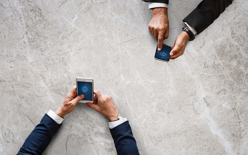 2 people holding mobile devices - international payments