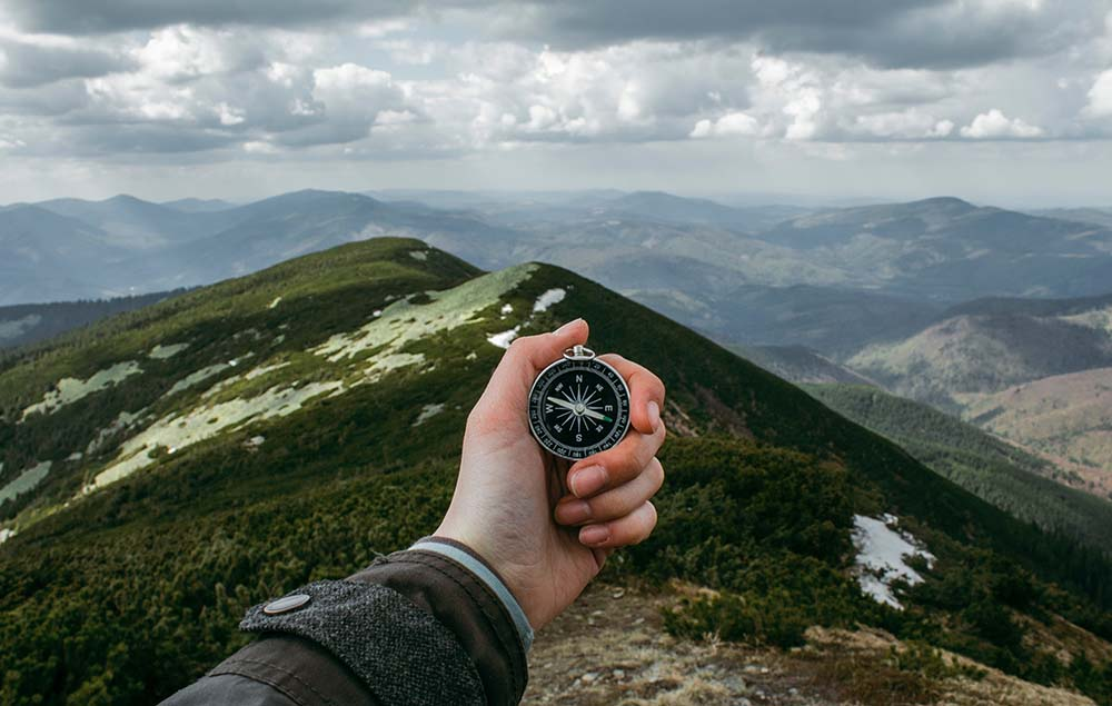 Hand holding a compass with mountain in background