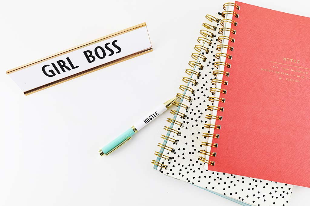 Notebooks and Girl Boss name plate on a white desk