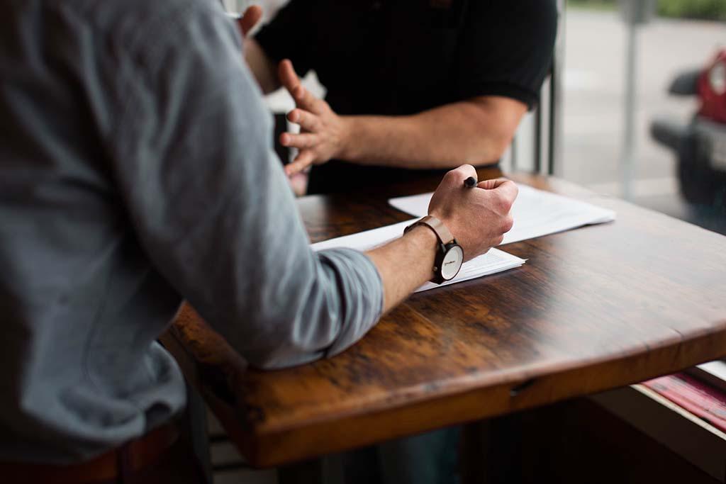2 men sitting facing each other at a desk - mentorship