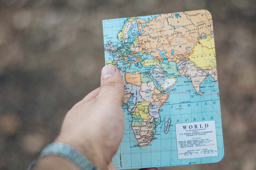 Man holds a notebook with image of world map