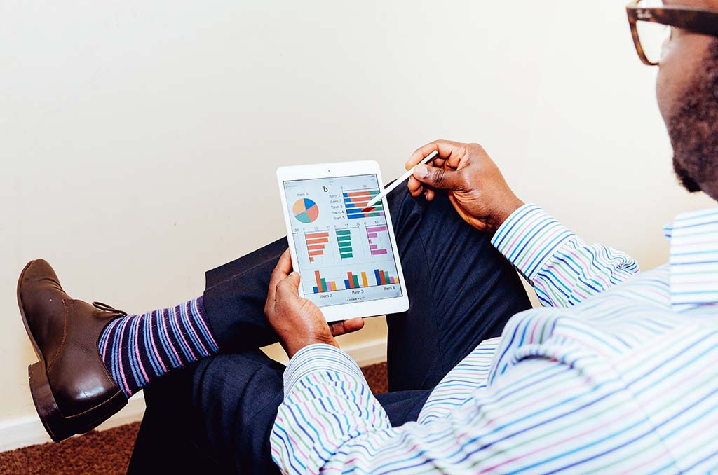 Man sitting in a chair reading a business report on a tablet