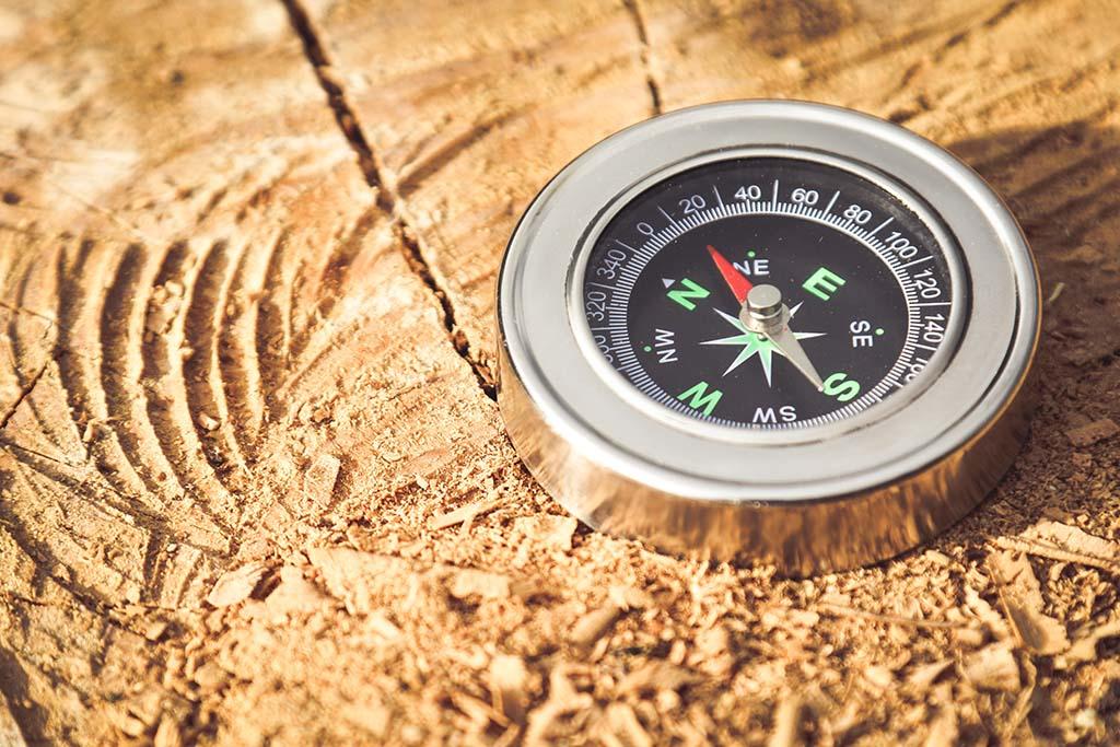 Compass lies on some sandy ground