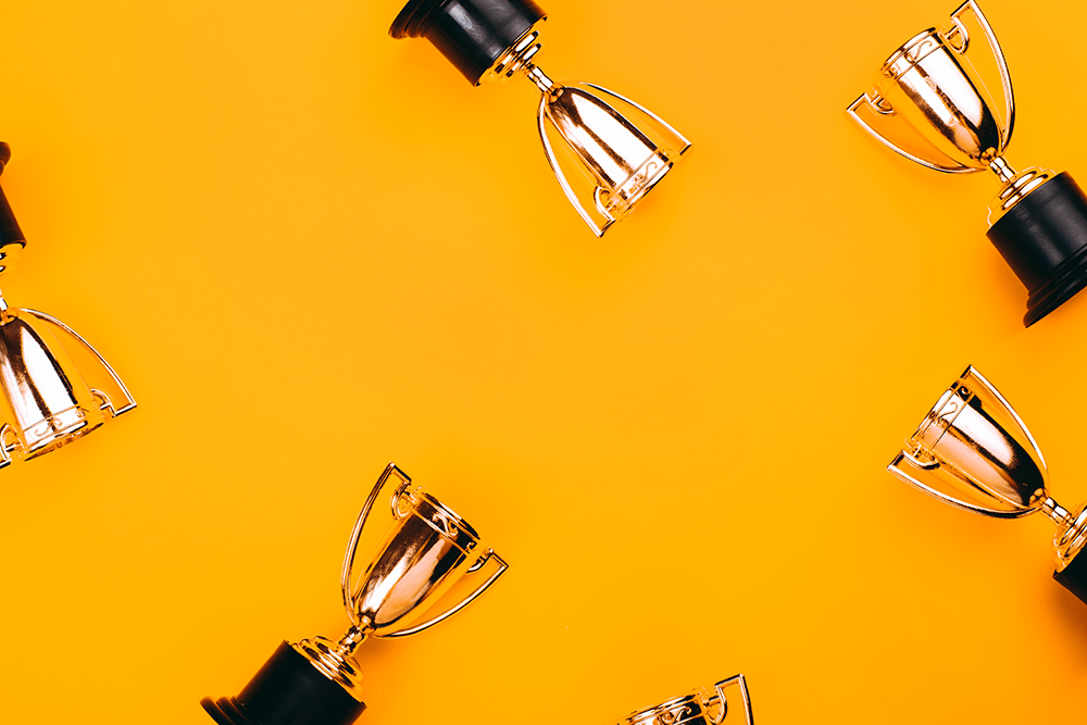 gold trophies on an orange background