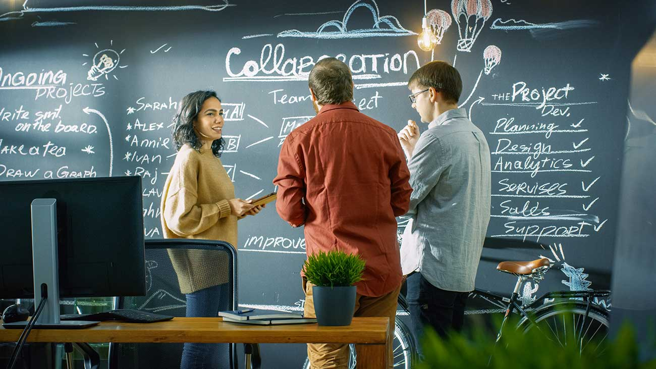 group of professionals talking by a blackboard