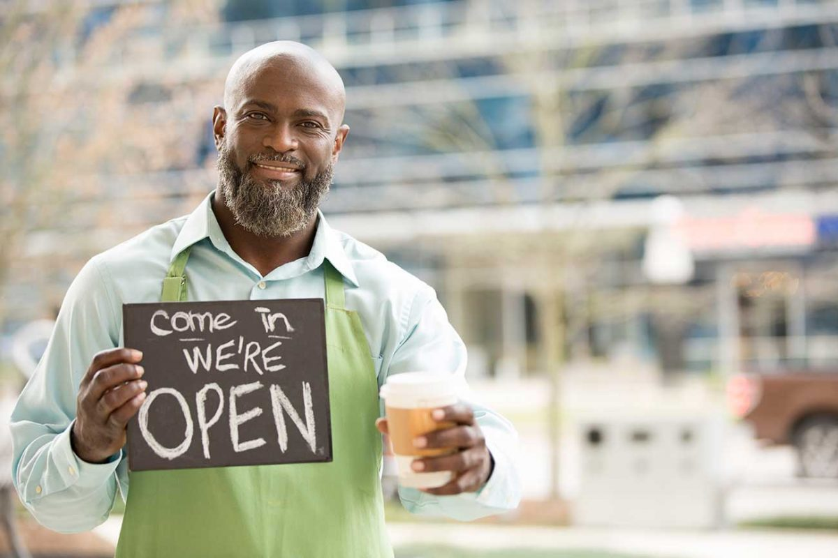 Business owner with open sign outside of coffee shop
