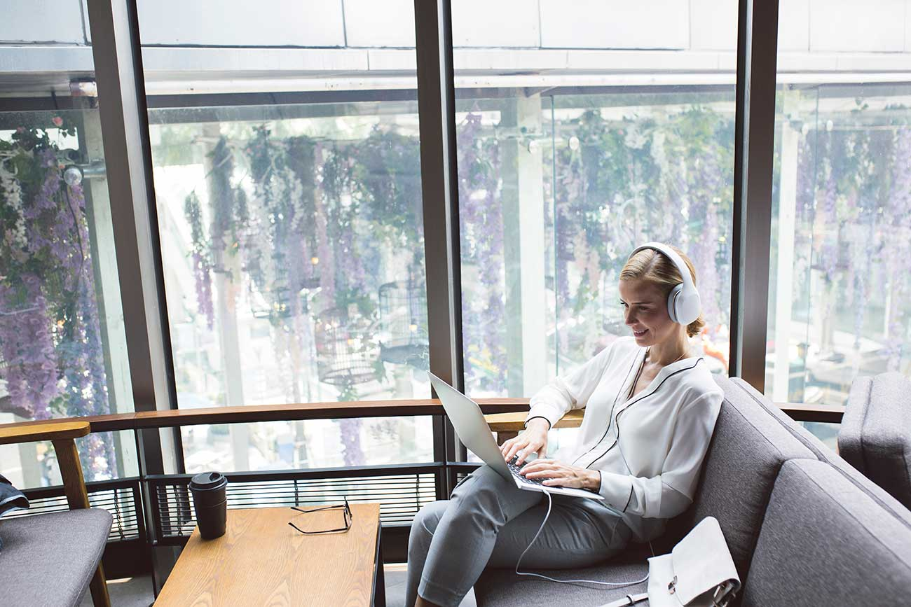 business woman on laptop with headphones on couch