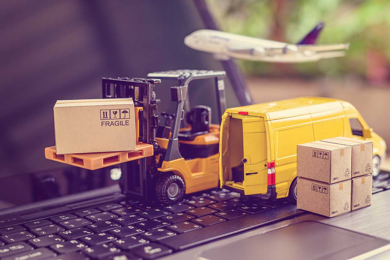 miniature forklift van and airplane on laptop keyboard delivering boxes