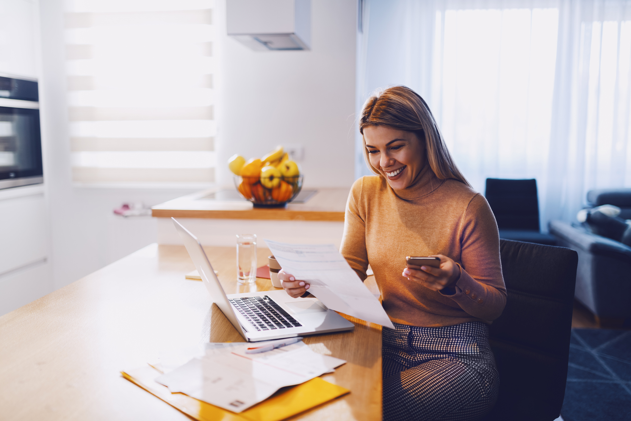 woman in sweater holding bills in one hand and in other smart phone. On table are laptop and bills